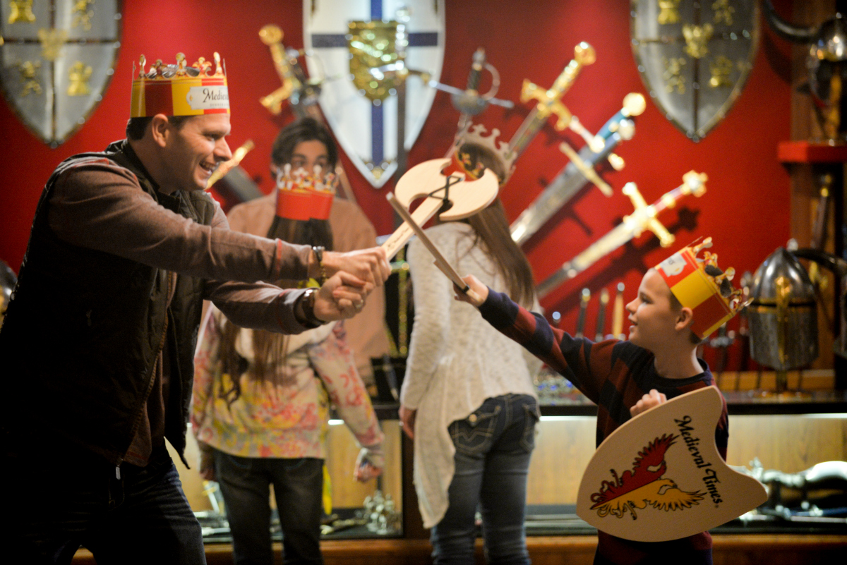 father and son playing with wooden swords and shields in the Hall of Arms
