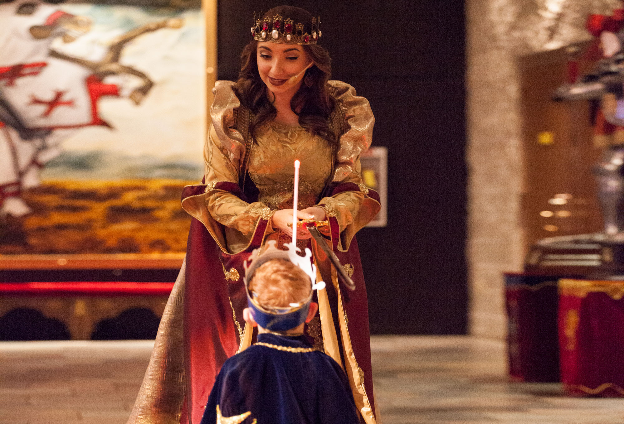 a boy getting knighted by the queen in the Hall of Arms
