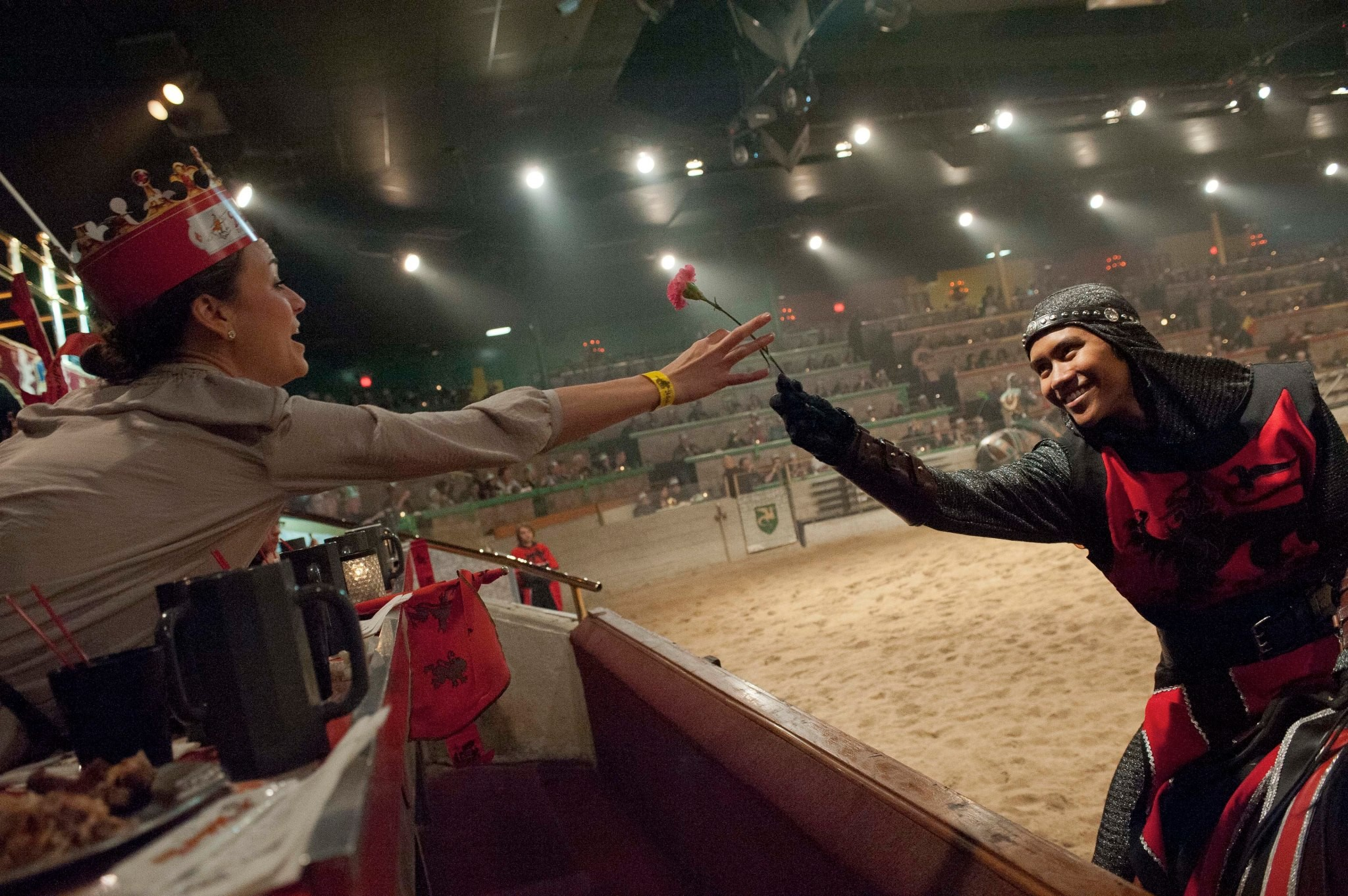 the red knight on horseback hands a carnation to a young woman sitting in the front row