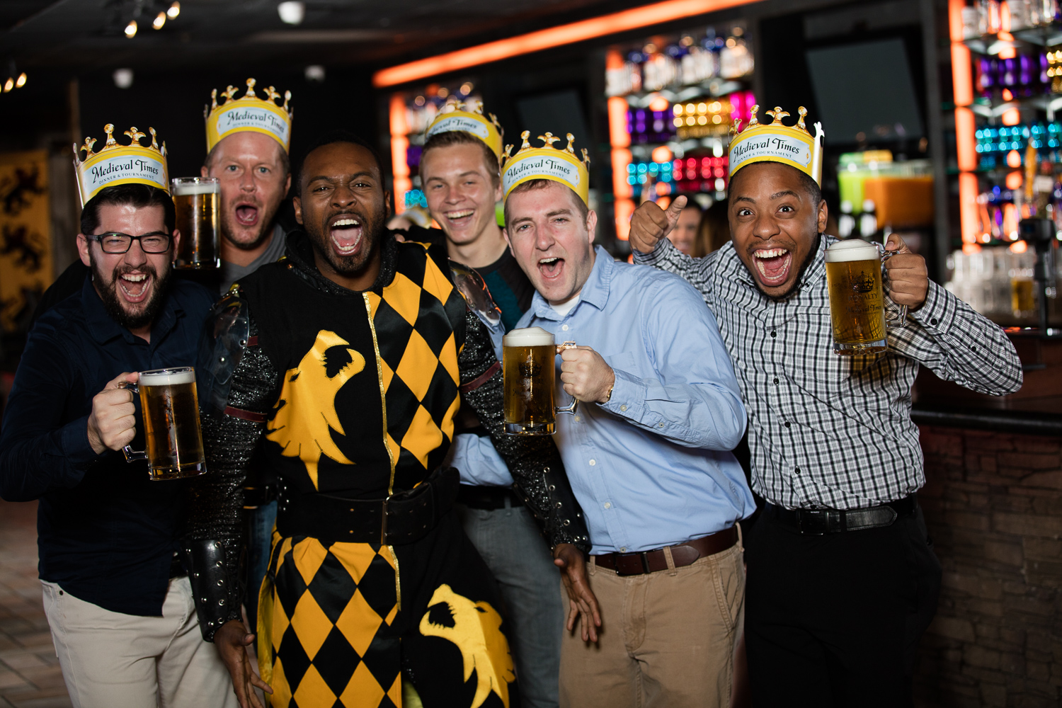 group of young men holding beverages by the bar posing with knight